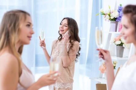 beautiful girlfriends in pajamas drinking champagne while friend talking by smartphone
