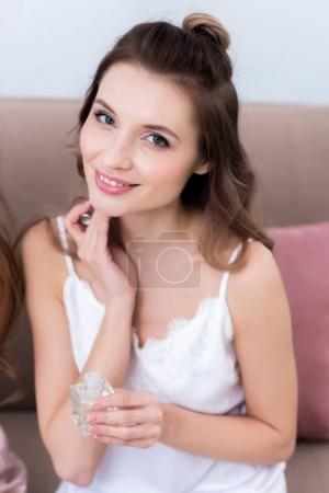 beautiful young woman holding bottle of perfume and smiling at camera