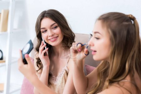 beautiful young women applying makeup and talking by smartphone at pajama party