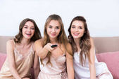 beautiful young women in pajamas using remote controller and smiling at camera