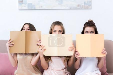 three attractive girlfriends holding magazines and looking at camera