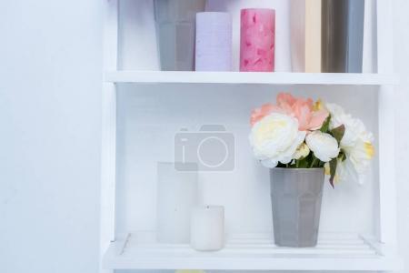 Photo pour Vue rapprochée des étagères en bois blancs avec des livres, des bougies et des fleurs dans un vase - image libre de droit