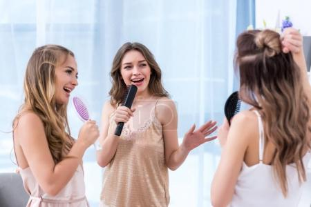 beautiful smiling young women in pajamas having fun and singing with hairbrushes