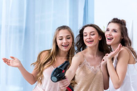 beautiful happy girlfriends in pajamas having fun and singing with hair dryer
