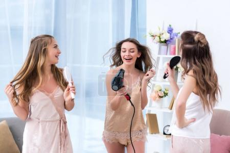 beautiful happy girlfriends in pajamas having fun and singing with hairbrushes and hair dryer