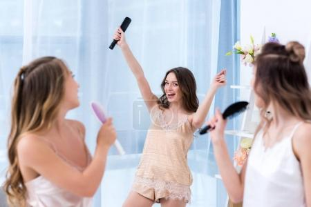 beautiful happy girlfriends in pajamas having fun and singing with hairbrushes