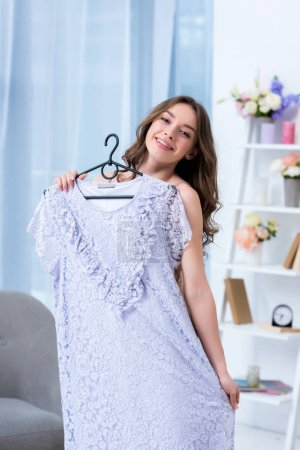 Photo for Attractive girl holding hanger with stylish dress and smiling at camera - Royalty Free Image