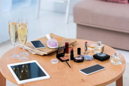 close-up view of digital devices, glasses of champagne and cosmetics on table