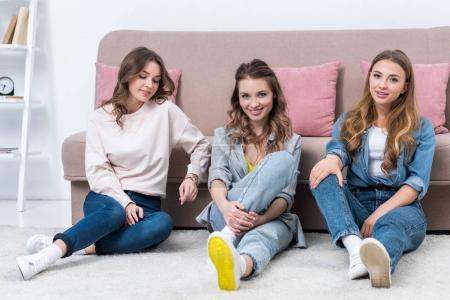 beautiful young women sitting on carpet and smiling at camera
