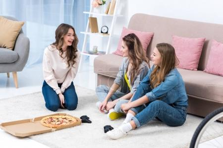 beautiful smiling young women talking and eating pizza at home