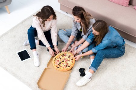 high angle view of beautiful young women eating pizza at home