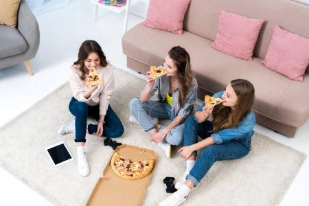 high angle view of beautiful smiling young women eating pizza at home