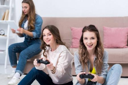 beautiful smiling young women playing with joysticks