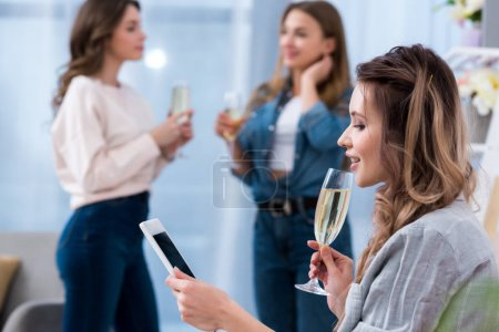 young woman holding glass of champagne and using smartphone while friends talking behind