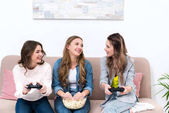 beautiful young girlfriends eating popcorn and playing with joysticks together at home
