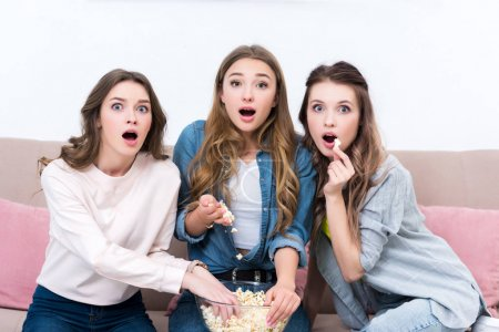 shocked young woman eating popcorn and watching movie together