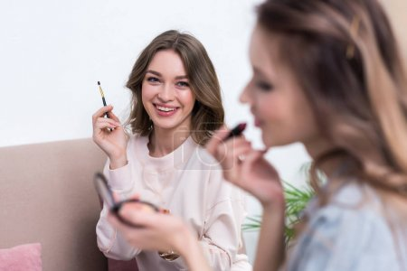 selective focus of smiling young women applying makeup together at home