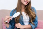 cropped shot of smiling young woman combing hair with hairbrush