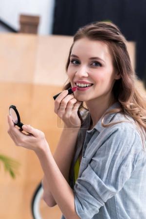 beautiful young woman applying makeup and smiling at camera