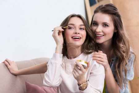 beautiful smiling young women applying makeup at home
