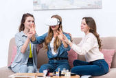 smiling young girlfriends having fun together with virtual reality headset