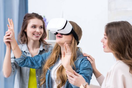 happy young girlfriends having fun together with virtual reality headset