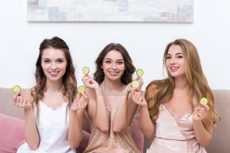 beautiful young women in pajamas holding cucumber slices and smiling at camera