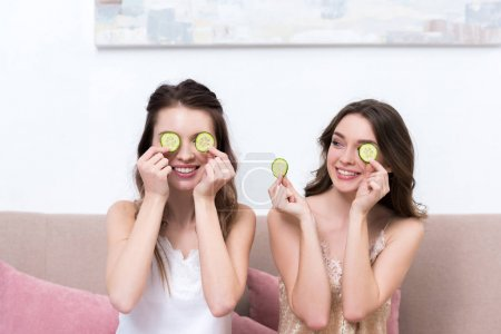 beautiful smiling girls in pajamas holding slices of cucumber near eyes