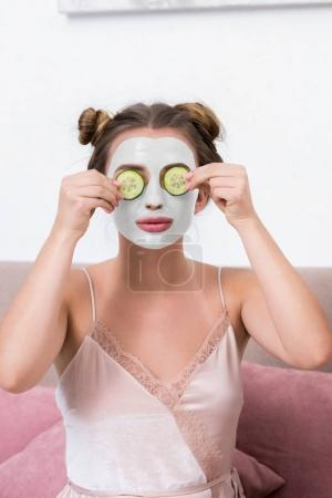 attractive young woman in pajama holding cucumber slices near face with mask