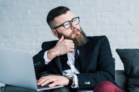 Photo pour Portrait d'homme d'affaires songeur en lunettes avec ordinateur portable à la recherche de suite - image libre de droit