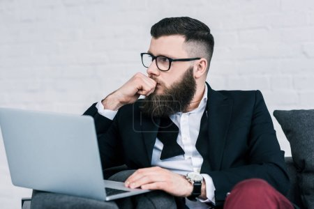 portrait of pensive businessman with laptop looking away