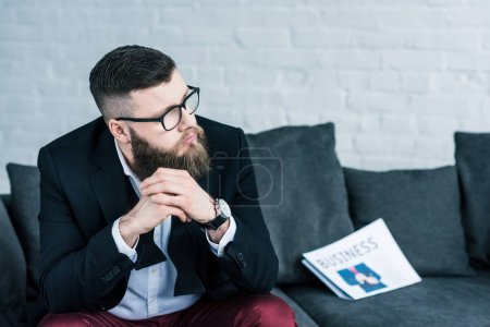 portrait of thoughtful businessman sitting on sofa with business newspaper