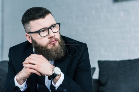 portrait of stylish thoughtful businessman in eyeglasses looking away