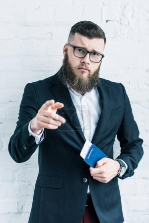 portrait of businessman with passport and ticket in hand pointing at camera