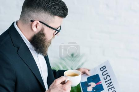 side view of businessman with cup of coffee and business newspaper in hands