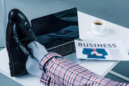 partial view of businessman with legs on tabletop with laptop and business newspaper
