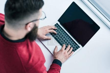 overhead view of businessman typing on laptop with blank screen