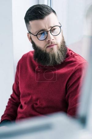 portrait of handsome pensive businessman in eyeglasses looking away