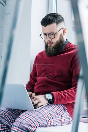 selective focus of focused businessman in eyeglasses working on laptop