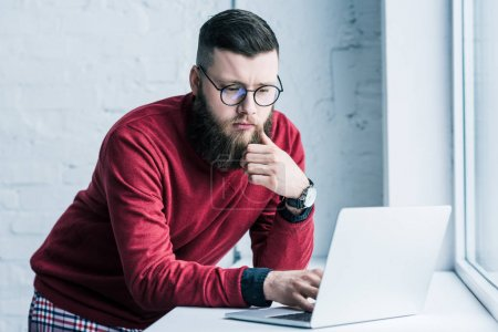 portrait of concentrated businessman in eyeglasses working on laptop