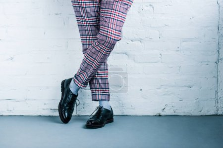 cropped shot of man in stylish pants and shoes standing against white brick wall