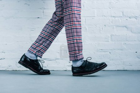 Photo for Cropped shot of man in stylish shoes walking against white brick wall - Royalty Free Image