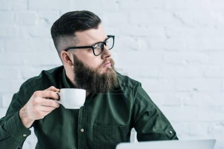 portrait of pensive businessman holding cup of coffee in hand