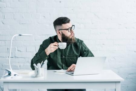 Photo for Portrait of pensive businessman with cup of coffee sitting at workplace with laptop - Royalty Free Image