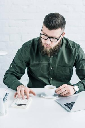 portrait of focused businessman making calculations at workplace with cup of coffee