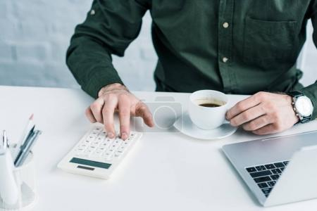 partial view of businessman making calculations at workplace with cup of coffee