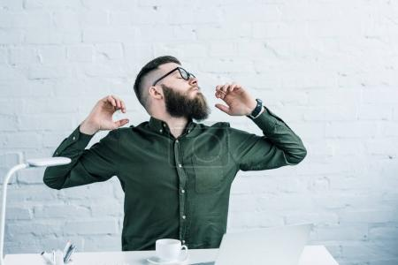 portrait of tired businessman stretching at workplace with laptop and cup of coffee