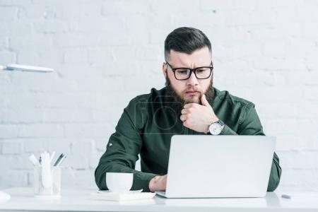 portrait of focused businessman working on laptop at workplace