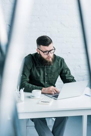 Photo for Portrait of focused businessman working on laptop at workplace - Royalty Free Image