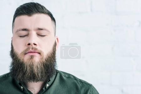 Photo pour Portrait d'un homme barbu les yeux fermés contre un mur de briques blanches - image libre de droit